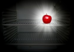 Conceptual creative photo of a glowing in the dark fresh red apple in an open empty refrigerator. Weight loss diet concept.