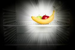 Conceptual creative photo of fresh red and green apples and banana glowing in the dark in an open empty refrigerator. Weight loss diet concept.