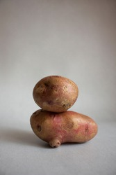 Conceptual creative still life with balancing fresh red potatoes on a light gray background. Equilibrium floating food balance. Trendy ugly organic unusual, funny vegetables and food waste for mockup.