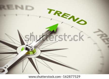 Conceptual 3D render image with depth of field blur effect. Compass needle pointing the green word trend over natural paper background.