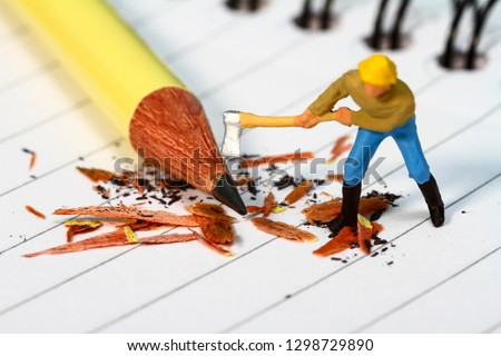 Conceptual diorama image of a miniature figure sharpening a pencil on a note book