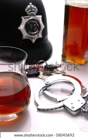 Conceptual \'driving under the influence of alcohol\' shot. High key scene of  handcuffs, british police hat, alcoholic drinks and car keys