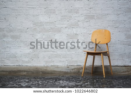 Conceptual Empty Wooden Leg Chairs with white wall and gray wooden floor and copyspace