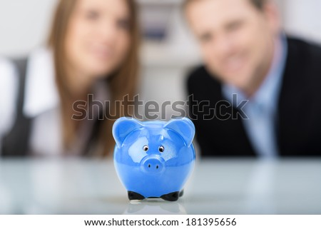 Conceptual financial image with a cute blue ceramic piggy bank sitting centered on a desk with a smiling successful professional couple in the background, focus to the piggy