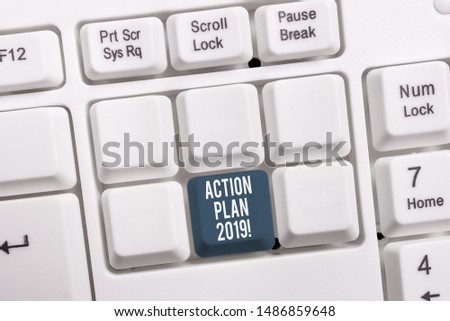 Conceptual hand writing showing Action Plan 2019. Business photo showcasing proposed strategy or course of actions for current year White pc keyboard with note paper above the white background.