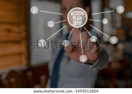 Conceptual hand writing showing Action Plan 2019. Business photo showcasing proposed strategy or course of actions for current year Woman wear suit presenting presentation using smart device.