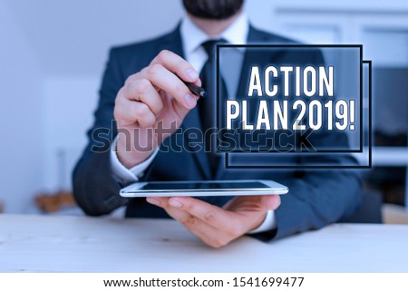 Conceptual hand writing showing Action Plan 2019. Business photo showcasing proposed strategy or course of actions for current year Male human wear formal clothes present use hitech smartphone. #1541699477