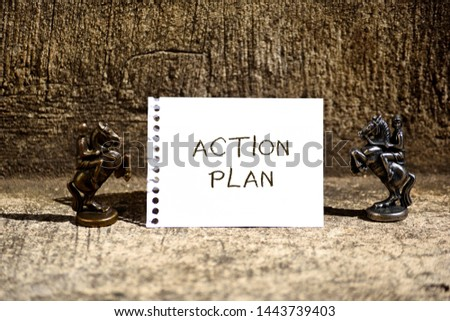 Conceptual hand writing showing Action Plan. Business photo showcasing proposed strategy or course of actions for certain time Two Bronze Chessmen Knights Ring Notepad Sheet Folded Half. #1443739403