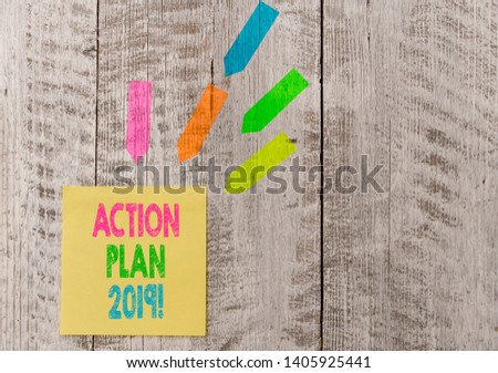 Conceptual hand writing showing Action Plan 2019. Business photo text proposed strategy or course of actions for current year Note paper and line arrow stickers on the top of wooden table desk. #1405925441