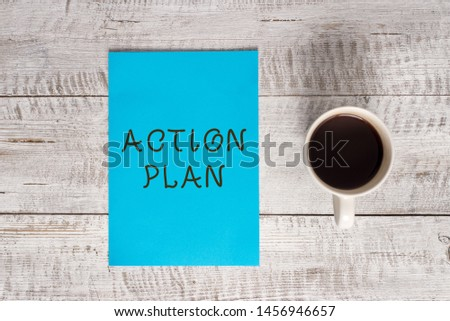 Conceptual hand writing showing Action Plan. Business photo text proposed strategy or course of actions for certain time Stationary placed next to a coffee cup above wooden table. #1456946657