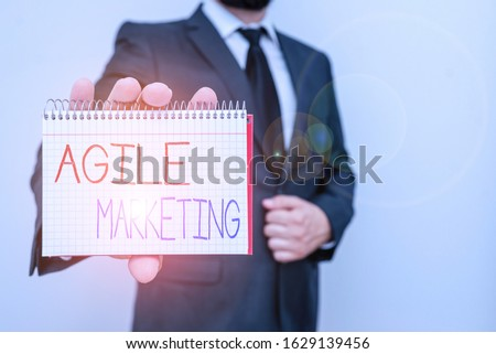 Conceptual hand writing showing Agile Marketing. Business photo text focusing team efforts that deliver value to the endcustomer Male human wear formal work suit with office look hold book.