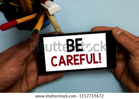 Conceptual hand writing showing Be Careful. Business photo showcasing making sure of avoiding potential danger mishap or harm Man holding cell phone looking messages apps cup markers. #1157719672