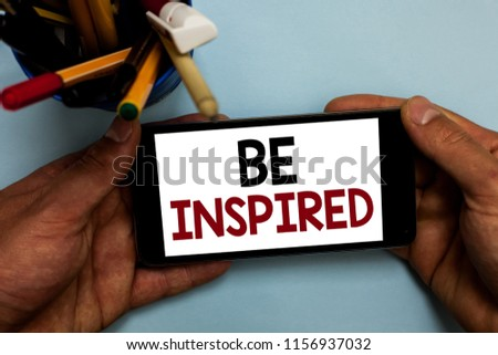 Conceptual hand writing showing Be Inspired. Business photo showcasing extraordinary quality as arising from some creative impulse Man holding cell phone looking messages apps cup markers. #1156937032