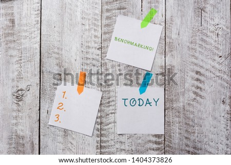 Conceptual hand writing showing Benchmarking. Business photo text evaluate something by comparison with standard or scores Plentiful of plain paper sheet attached with wooden textured table. #1404373826