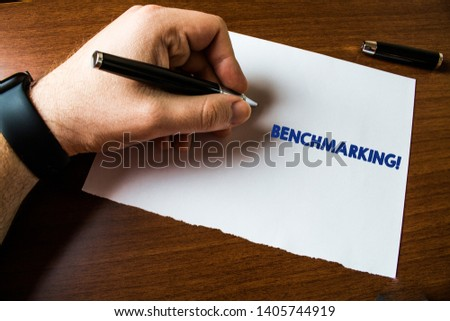 Conceptual hand writing showing Benchmarking. Business photo text evaluate something by comparison with standard or scores Man left hand watch paper ballpoint Pen cap lying wooden table. #1405744919