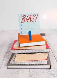 Conceptual hand writing showing Bias. Business photo showcasing inclination or prejudice for or against one demonstrating group pile stacked books notebook pin color reminder white wooden.