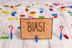 Conceptual hand writing showing Bias. Business photo text inclination or prejudice for or against one demonstrating group Crumbling sheet with paper clips placed on the wooden table.