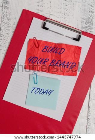 Conceptual hand writing showing Build Your Brand. Business photo showcasing enhancing brand equity using advertising campaigns Clipboard paper crushed sticky note clip wooden background.
