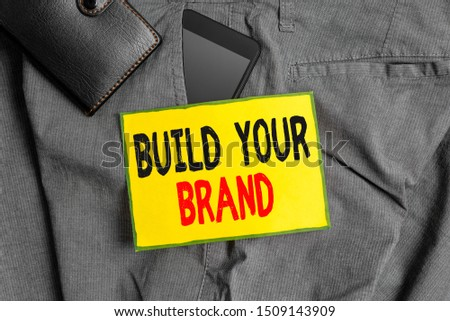 Conceptual hand writing showing Build Your Brand. Business photo showcasing enhancing brand equity using advertising campaigns Smartphone device inside trousers front pocket with wallet.