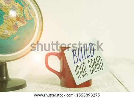Conceptual hand writing showing Build Your Brand. Business photo showcasing enhancing brand equity using advertising campaigns Globe map coffee cup sticky note lying vintage wooden table.