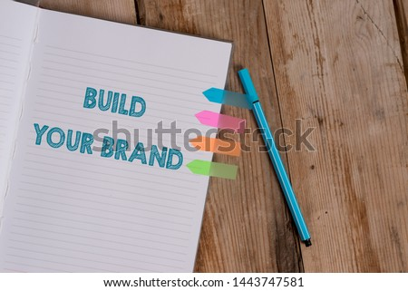 Conceptual hand writing showing Build Your Brand. Business photo text enhancing brand equity using advertising campaigns Striped notebook colored arrow banners ballpoint wooden background.