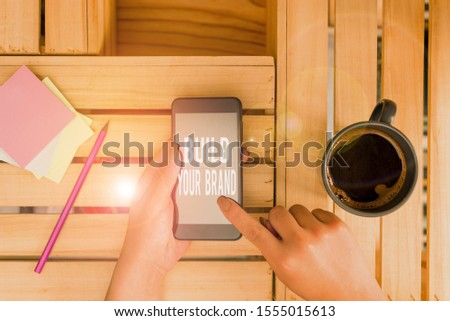Conceptual hand writing showing Build Your Brand. Business photo text enhancing brand equity using advertising campaigns woman with laptop smartphone and office supplies technology.
