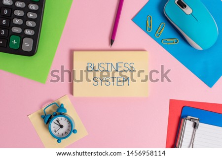 Conceptual hand writing showing Business System. Business photo text A method of analyzing the information of organizations Mouse calculator sheets marker clipboard clock color background. #1456958114