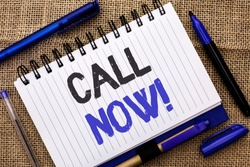 Conceptual hand writing showing Call Now. Business photo showcasing Contact Talk Chat Hotline Support Telephony Customer Service written on Notebook Book on jute background Pens next to it.