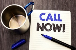 Conceptual hand writing showing Call Now. Business photo showcasing Contact Talk Chat Hotline Support Telephony Customer Service written on Notebook Paper wooden background Marker and Cup