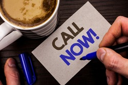 Conceptual hand writing showing Call Now. Business photo text Contact Talk Chat Hotline Support Telephony Customer Service written Man Holding Marker on Note Paper Wooden background Coffee.