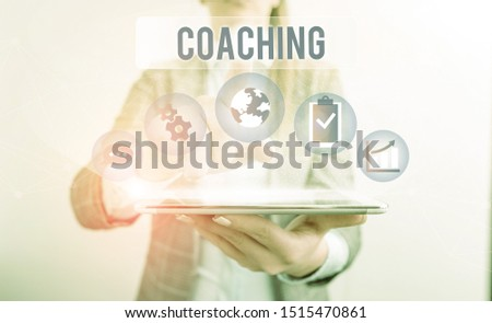 Conceptual hand writing showing Coaching. Business photo showcasing demonstrating supports client in achieving specific demonstratingal goal Female human wear formal work suit presenting smart device.