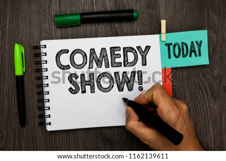 Conceptual hand writing showing Comedy Show. Business photo showcasing Funny program Humorous Amusing medium of Entertainment Man holding marker notebook reminder cup markers wood table.