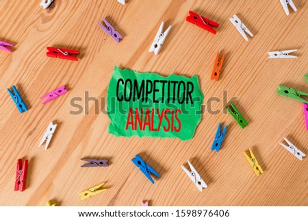 Conceptual hand writing showing Competitor Analysis. Business photo showcasing assessment of the strengths and weaknesses of rival firm Colored crumpled papers wooden floor background clothespin.