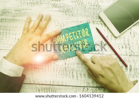 Conceptual hand writing showing Competitor Analysis. Business photo text assessment of the strengths and weaknesses of rival firm Hand hold note paper near writing equipment and smartphone.