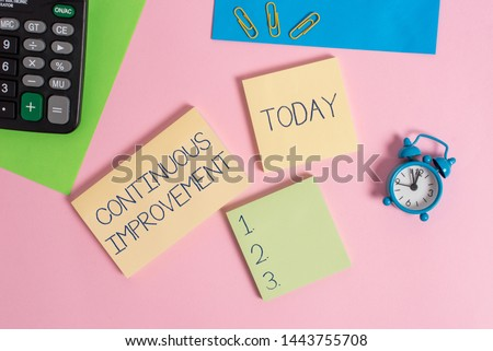 Conceptual hand writing showing Continuous Improvement. Business photo showcasing ongoing effort to improve products or processes Alarm clock calculator notepads paper sheet color background.