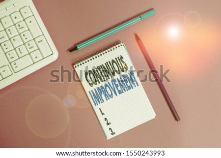 Conceptual hand writing showing Continuous Improvement. Business photo showcasing ongoing effort to improve products or processes Writing equipments and computer stuff placed on plain table.