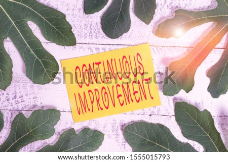 Conceptual hand writing showing Continuous Improvement. Business photo text ongoing effort to improve products or processes Leaves surrounding notepaper above a classic wooden table.