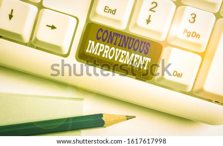 Conceptual hand writing showing Continuous Improvement. Business photo text ongoing effort to improve products or processes White pc keyboard with note paper above the white background.