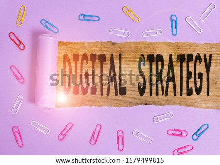 Conceptual hand writing showing Digital Strategy. Business photo showcasing plan for maximizing the business benefits of data assets Paper clip and torn cardboard on wood classic table backdrop.