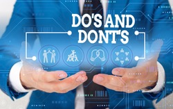Conceptual hand writing showing Do S And Dont S. Business photo showcasing Rules or customs concerning some activity or actions Male wear formal suit presenting presentation smart device.