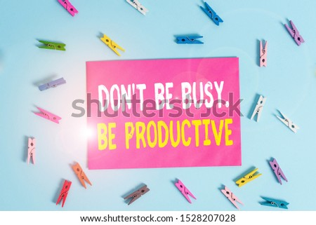 Conceptual hand writing showing Don T Be Busy Be Productive. Business photo showcasing Work efficiently Organize your schedule time Colored clothespin rectangle shaped paper blue background. #1528207028