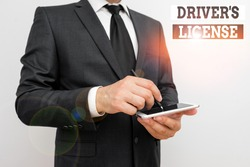 Conceptual hand writing showing Driver S License. Business photo text a document permitting a demonstrating to drive a motor vehicle Male human wear formal work suit hold smartphone using hand.