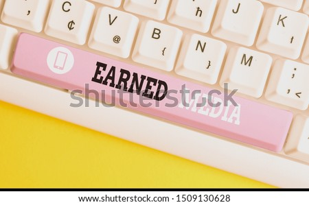 Conceptual hand writing showing Earned Media. Business photo showcasing Publicity gained through promotional efforts by multimedia White pc keyboard with note paper above the white background.