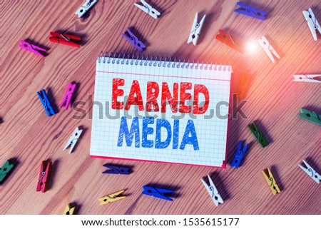 Conceptual hand writing showing Earned Media. Business photo text Publicity gained through promotional efforts by multimedia Colored crumpled papers wooden floor background clothespin.