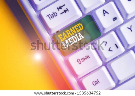 Conceptual hand writing showing Earned Media. Business photo text Publicity gained through promotional efforts by multimedia White pc keyboard with note paper above the white background.