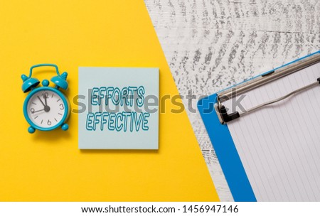 Conceptual hand writing showing Efforts Effective. Business photo showcasing Produces the results as per desired Goal Target Achieve Notepad colored paper sheet alarm clock wooden background.