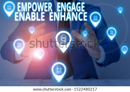 Conceptual hand writing showing Empower Engage Enable Enhance. Business photo showcasing Empowerment Leadership Motivation Engagement Male wear formal suit presenting presentation smart device.