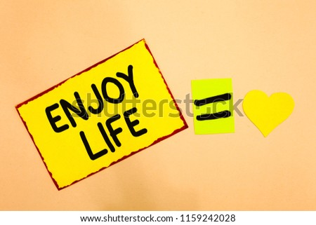 Conceptual hand writing showing Enjoy Life. Business photo text Any thing, place,food or person, that makes you relax and happy Yellow paper reminder equal sign heart sending romantic feelings. #1159242028