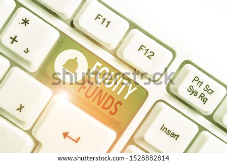 Conceptual hand writing showing Equity Funds. Business photo showcasing type of mutual fund that buys ownership in businesses White pc keyboard with note paper above the white background.