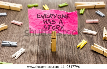 Conceptual hand writing showing Everyone Has A Story. Business photo showcasing Background storytelling telling your memories tales Paperclip hold pink note with texts many clips wooden floor.